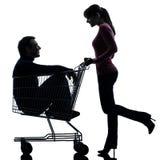 Junte a la mujer con el hombre que se sienta en silueta del carro de la compra Imagenes de archivo