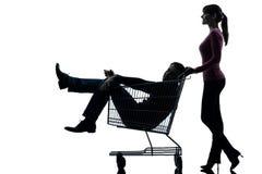 Junte a la mujer con el hombre que se sienta en silueta del carro de la compra Foto de archivo libre de regalías