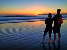 Junte la observación de una puesta del sol colorida a lo largo de la línea de la playa de la playa fotos de archivo libres de regalías