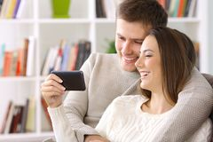 Junte la observación en la línea contenido en un teléfono elegante en casa Imágenes de archivo libres de regalías