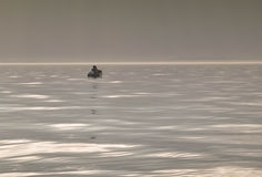 Junte la pesca en un bote pequeño en un día de niebla Imagenes de archivo
