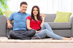Junte la presentación asentada en una alfombra por un sofá en casa Foto de archivo libre de regalías