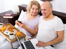 Junte la presentación con el desayuno y el ordenador portátil en cama Imágenes de archivo libres de regalías