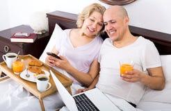 Junte la presentación con el desayuno y el ordenador portátil en cama Fotografía de archivo