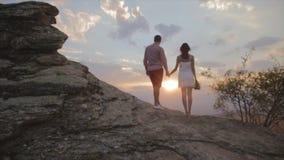 Junte la puesta del sol de observación en el top de la montaña que se coloca en la roca grande almacen de video