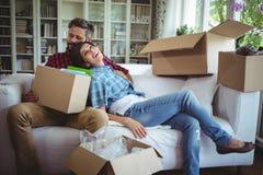 Junte la relajación en el sofá mientras que desempaqueta las cajas del cartón imagenes de archivo