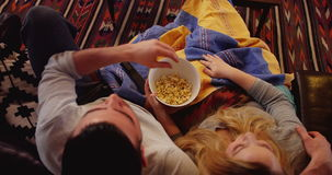 Junte la relajación en el sofá que ve la TV en sala de estar almacen de metraje de vídeo