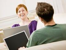 Junte la relajación en la sala de estar que pulsa en las computadoras portátiles Fotos de archivo libres de regalías