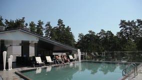 Junte la relajación en ociosos del sol cerca de la piscina almacen de metraje de vídeo