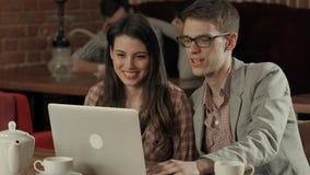 Junte la risa y tener de una conferencia video sobre un ordenador portátil, mientras que fuma la cachimba Imagen de archivo libre de regalías