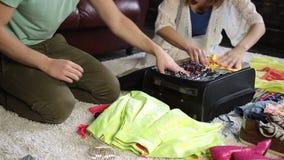 Junte la ropa del embalaje en la maleta para el viaje almacen de metraje de vídeo