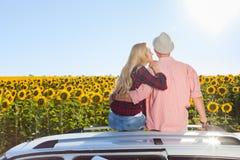 Junte la salida del sol del campo de los girasoles del tejado del coche del abrazo que se sienta Fotografía de archivo