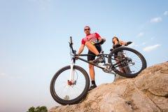 Junte la situación con las bicicletas en la roca debajo del cielo de la tarde Fotos de archivo