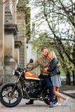 Junte la situación y el abarcamiento cerca de la motocicleta en el viejo fondo de la ciudad Foto de archivo libre de regalías
