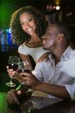 Junte la sonrisa y tostar sus copas de vino en el contador de la barra Fotos de archivo