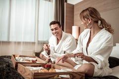 Junte las albornoces blancas que llevan que gozan del desayuno en la habitación foto de archivo libre de regalías