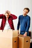 Junte las cajas unpaking, mujer que mira a la tenencia interior y horrorizada su cabeza Imagen de archivo libre de regalías