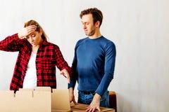 Junte las cajas unpaking, mujer que mira a la tenencia interior y horrorizada su cabeza Imagen de archivo
