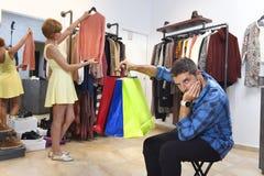 Junte las compras así como esperar del hombre agujereado frustrado mientras que la muchacha está cabiendo la ropa Foto de archivo libre de regalías
