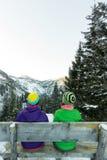 Junte a las muchachas de los turistas que se sientan en un banco en el invierno y que miran las montañas Fotos de archivo libres de regalías
