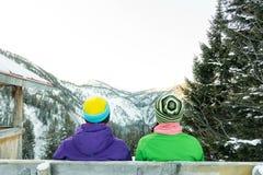 Junte a las muchachas de los turistas que se sientan en un banco en el invierno y que miran las montañas Imagenes de archivo