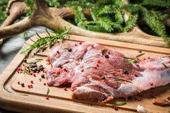 Junte las piezas de la carne de venado en el fondo de la picea y de astas Imagen de archivo
