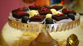 Junte las piezas de las semillas adornadas de la granada de la torta de chocolate y del caramelo dulce en una celebración hermosa metrajes