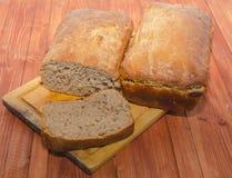 Junte las piezas y dos panes de pan fresco en una tabla de madera Imagenes de archivo