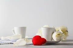 Junte las tazas blancas con la decoración por los corazones rojos en la tabla de madera Foto de archivo