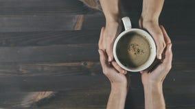 Junte llevar a cabo la taza de cocer el café al vapor en manos en fondo de madera almacen de metraje de vídeo