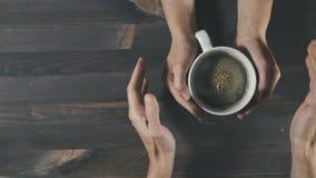 Junte llevar a cabo la taza de cocer el café al vapor en manos en el fondo de madera, visión superior almacen de video