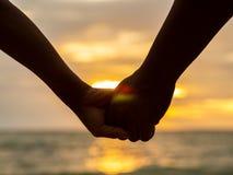 Junte llevar a cabo las manos en fondo hermoso de la puesta del sol en la playa imágenes de archivo libres de regalías