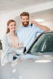 Junte llevar a cabo llave y la situación del coche en el coche en salón de la representación fotografía de archivo libre de regalías