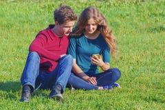 Junte a los adolescentes que se sientan en el césped verde con un smartphone Foto de archivo