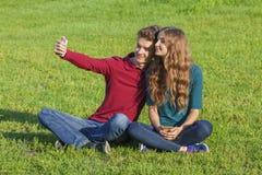 Junte a los adolescentes que se sientan en el césped verde con un smartphone Fotos de archivo