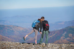 Junte a los caminantes con las mochilas en el canto de la montaña Imagen de archivo