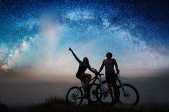 Junte a los ciclistas con las bicis de montaña en la noche debajo del cielo estrellado Imágenes de archivo libres de regalías