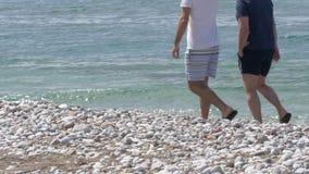 Junte a los hombres en pantalones cortos que caminan cerca del mar Mediterráneo claro en la playa blanca de la piedra de la arena metrajes