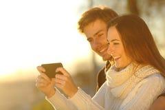 Junte los medios vídeos de observación en un teléfono elegante Fotos de archivo libres de regalías