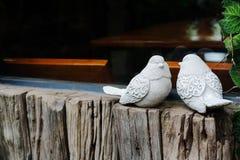 Junte los pájaros, dos estatuas blancas del pájaro en la ventana cercana de madera fotografía de archivo