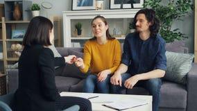 Junte los papeles de firma que toman llave del agente inmobiliario que se besa y que abraza en nuevo hogar metrajes