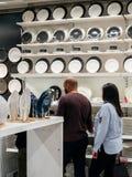 Junte los platos de compra y el dishware porcelan en las compras de IKEA Imágenes de archivo libres de regalías