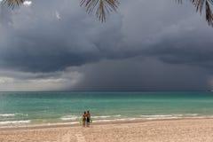 Junte los soportes en la playa y vea cómo está viniendo un tsunami Imagen de archivo libre de regalías