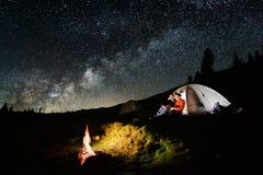Junte a los turistas cerca de hoguera y de tiendas debajo del cielo nocturno por completo de estrellas y de la vía láctea foto de archivo