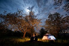 Junte a los turistas que se sientan en una hoguera cerca de la tienda debajo de árboles y del cielo nocturno con la luna El acamp fotografía de archivo libre de regalías