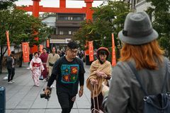 Junte a los turistas vestidos de moda de la juventud que caminan con la cámara al templo Kyoto foto de archivo