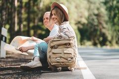 Junte a los viajeros mujer y hombre que se sientan en el camino y que miran adelante a un viaje común imagen de archivo libre de regalías