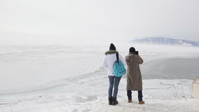 Junte a los viajeros que visitan el lago con las montañas en invierno y tome las imágenes almacen de metraje de vídeo