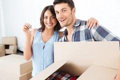 Junte mostrar llaves al nuevo hogar que abraza mirando la cámara imágenes de archivo libres de regalías