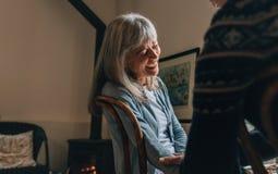 Junte sentar en casa hablar el uno al otro Mujer mayor que ríe mientras que teniendo una conversación con una persona en casa imagen de archivo
